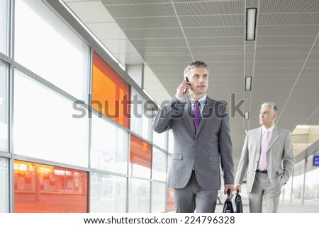 Middle aged businessman on call while walking in railroad station - stock photo