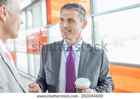 Middle aged businessman talking with male colleague in railroad station - stock photo