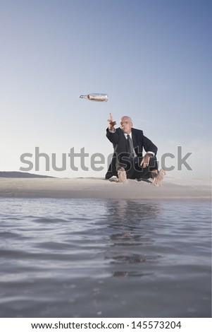 Middle aged businessman throwing bottle with message into sea at beach - stock photo