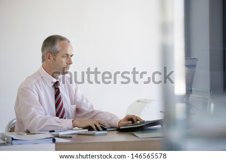 Middle aged businessman using computer at office desk - stock photo