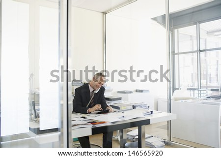Middle aged businessman using telephone and calculator at office desk - stock photo