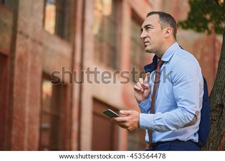Middle aged businessman using telephone outside - stock photo