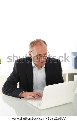 Middle-aged businessman with laptop Middle-aged businessman wearing glasses sitting at his desk working on his laptop with copyspace