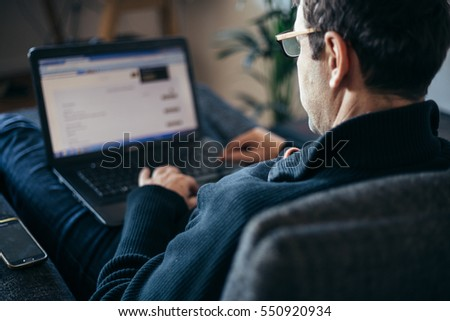 Middle aged businessman working from home comfortable in armchair