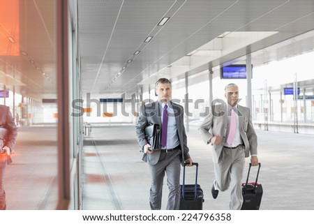 Middle aged businessmen with luggage rushing on railroad platform - stock photo