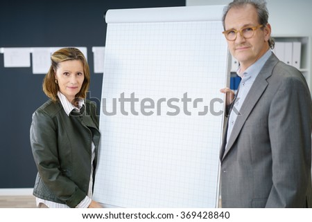 middle-aged businesspeople standing beside the chart giving a presentation or workshop - stock photo