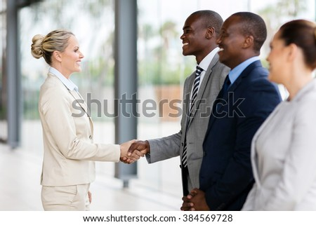 middle aged businesswoman handshaking with group of employees in office - stock photo