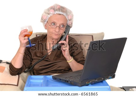 Middle aged businesswoman in bed, laptop on tray, making a phone call.  Glass of fruit juice in right hand - stock photo