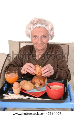 Middle aged businesswoman in pajamas having breakfast in bed, curlers and net in hair.