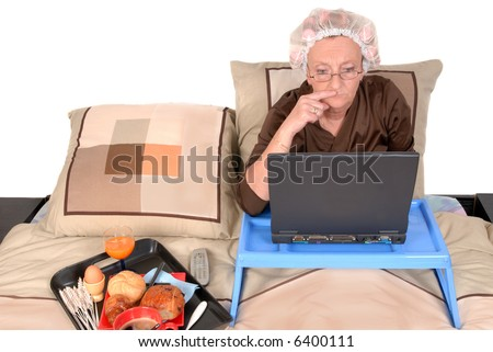 Middle aged businesswoman in pyjamas working at home in bed, laptop on tray.  Tray with breakfast on the side