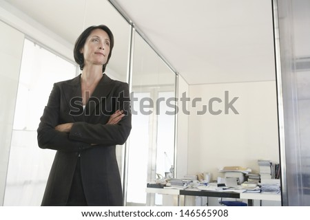 Middle aged businesswoman standing arms crossed in office - stock photo