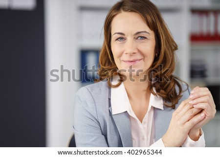 Middle-aged businesswoman with a natural friendly smile sitting looking into the camera with her clasped hands in front of her - stock photo