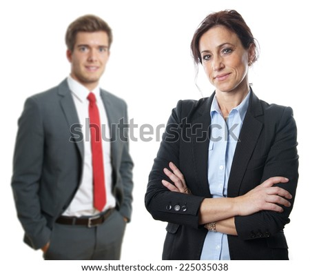 middle aged businesswoman with younger businessman in the background - stock photo