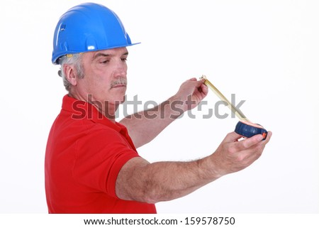 Middle-aged carpenter holding tape measure - stock photo