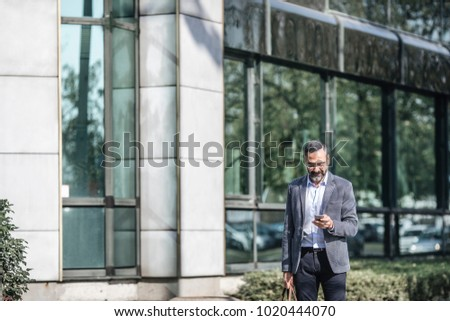 Middle-aged Caucasian businessman standing outdoors and typing on his cell phone.