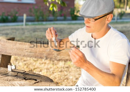 Middle-aged Caucasian man filling a syringe with addictive soluble crack cocaine - stock photo