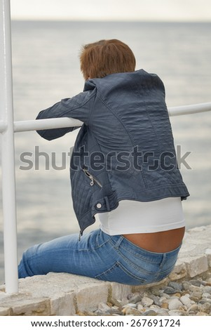 Middle aged caucasian tanned woman in autumn clothing sitting on the rocky sea beach - stock photo