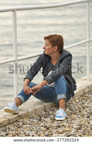 Middle aged caucasian tanned woman in autumn clothing sitting on the rocky sea beach