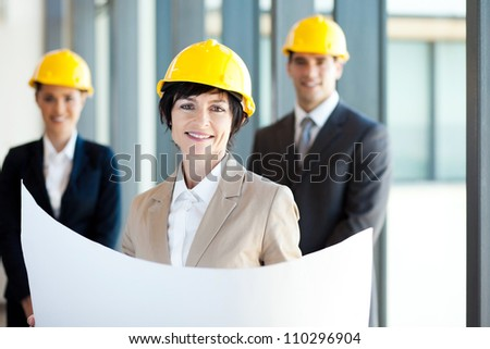 middle aged construction businesswoman holding blue print in front of colleagues - stock photo