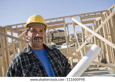 Middle aged construction worker holding blueprints