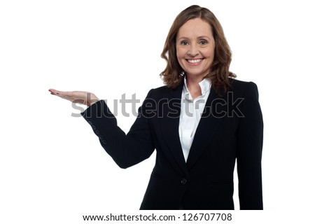 Middle aged corporate woman showing copy space to the camera, smiling warmly.