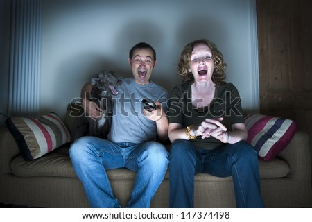 middle aged couple and dog laughing at the television - stock photo