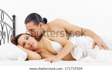 Middle-aged couple awaking in bed at home
