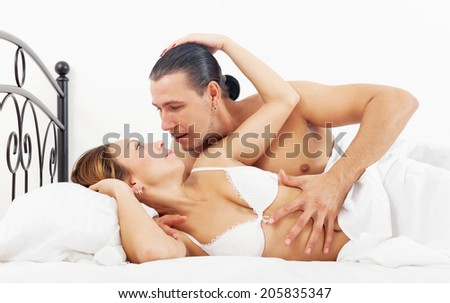Middle-aged couple awaking together in bed at bedroom