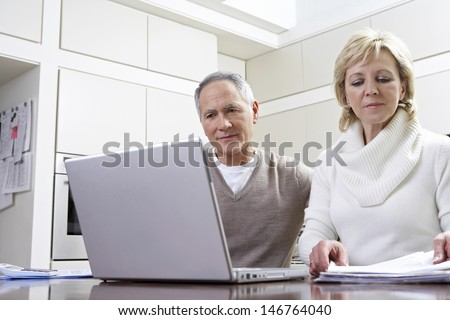 Middle aged couple calculating home finances on laptop at kitchen table - stock photo