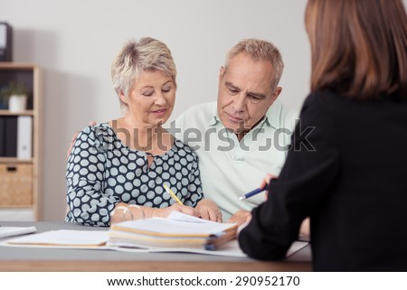 Middle Aged Couple Discussing Something on the Document to a Female Agent at the Table. - stock photo
