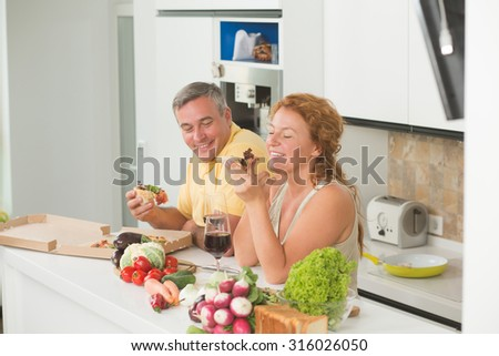 Middle-aged couple eating pizza in the modern kitchen. Cheerful man and woman having fun indoor. - stock photo