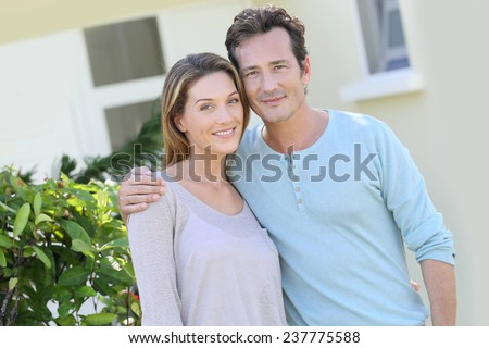 Middle-aged couple embracing in front of house - stock photo