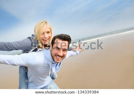 Middle-aged couple having fun on a sandy beach - stock photo