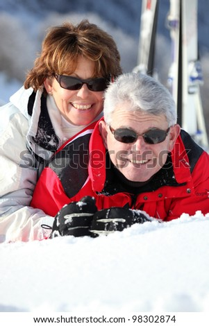 Middle-aged couple having fun on their skiing holiday - stock photo