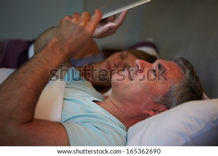 Middle Aged Couple In Bed With Man Using Tablet Computer - stock photo