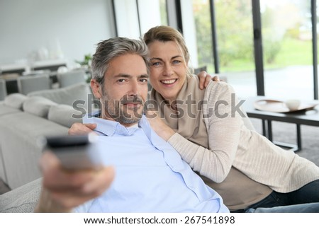 Middle-aged couple in living-room watching television - stock photo