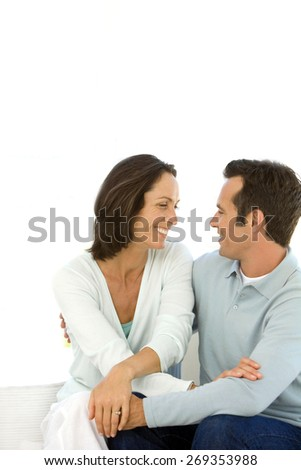 Middle aged couple in love hugging on sofa - stock photo