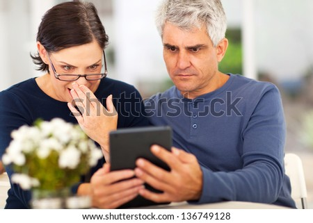 middle aged couple reading shocking news on tablet computer - stock photo