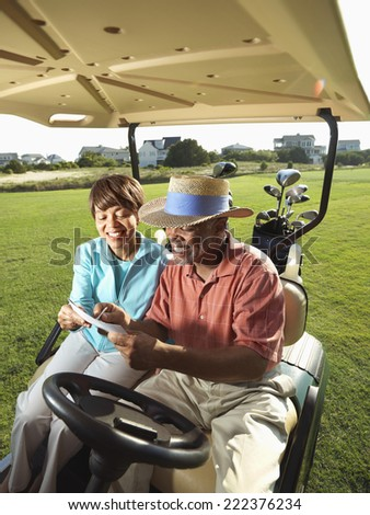 Middle-Aged Couple Riding a Golf Cart - stock photo