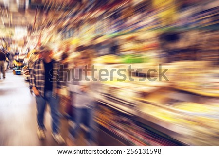Middle aged couple shopping for groceries in a public market -  radial zoom effect defocusing filter applied, with vintage instagram look - stock photo