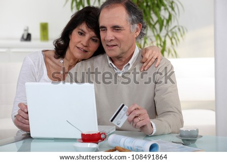 Middle-aged couple shopping on-line - stock photo
