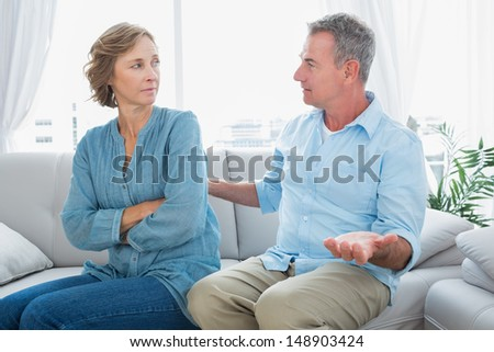Middle aged couple sitting on the sofa having a dispute at home in the living room - stock photo