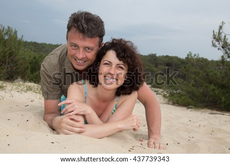Middle-aged couple smiling at the beach on sand