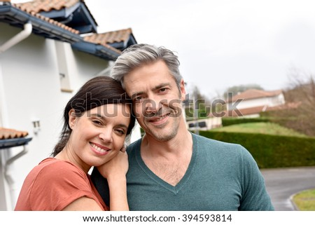 Middle-aged couple standing in front of new home - stock photo