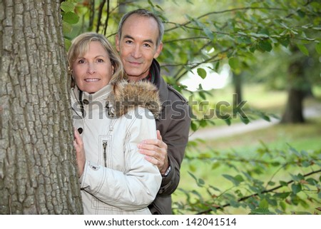 Middle-aged couple strolling in a public park - stock photo