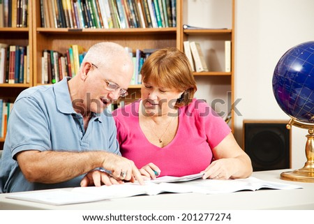 Middle-aged couple studying together in the library.   - stock photo