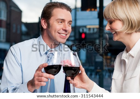 Middle aged couple toasting red wine at an outdoor cafe - stock photo