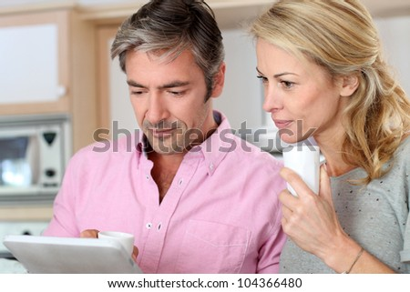 Middle aged couple using tablet in kitchen - stock photo