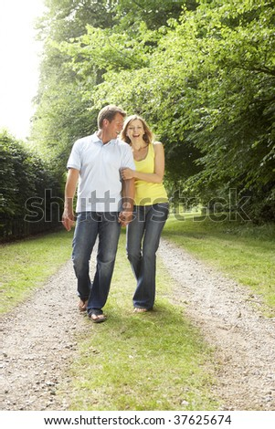 Middle aged couple walking in countryside - stock photo