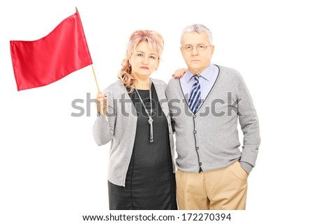 Middle aged couple waving a red flag, isolated on white background - stock photo